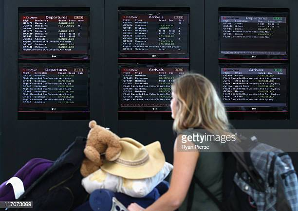 A passenger walks past a departures screen as airlines cancel flights due to volcanic ash at Sydney Domestic Airport on June 21 2011 in Sydney...