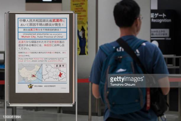 A passenger walks past a notice for passengers from Wuhan China displayed near a quarantine station at Narita airport on January 17 2020 in Narita...