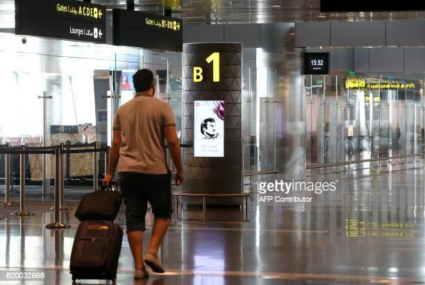 A passenger walks past a portrait of the Qatari Emir in the departures lounge at the Hamad International Airport in Doha on July 20 2017 / AFP PHOTO...