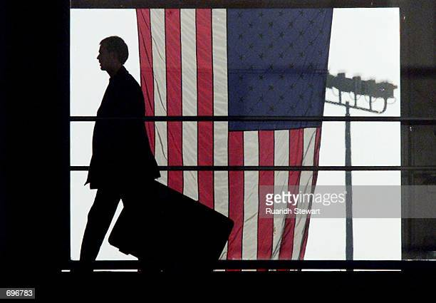 A passenger walks past a US flag at the entrance of the San Diego airport February 12 2002 in San Diego CA The FBI has issued a warning of possible...
