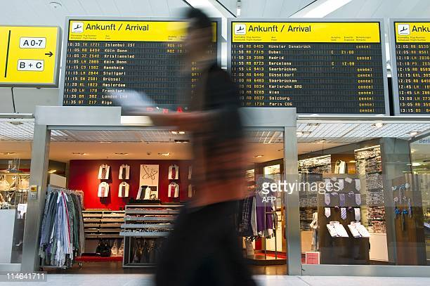A passenger walks past an electronic billboard that shows cancelled flights in the main hall of Berlin's Tegel airport on May 25 2011 An ash cloud...