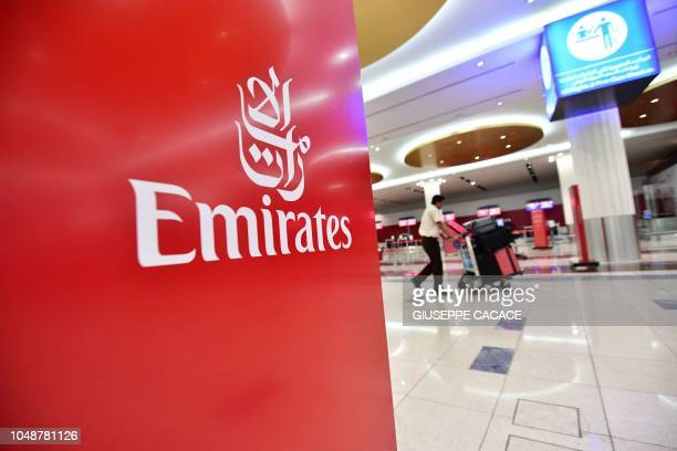 A passenger walks past an Emirates airlines logo at Dubai International Airport's T3 in the United Arab Emirates on October 10 2018