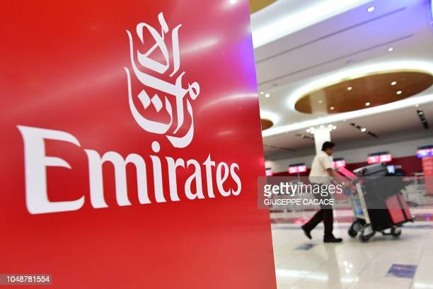 A passenger walks past an Emirates airlines logo at Dubai International Airport's terminal 3 in the United Arab Emirates on October 10 2018