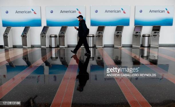 A passenger walks past empty American Airlines checkin terminals at Ronald Reagan Washington National Airport in Arlington Virginia on May 12 2020...