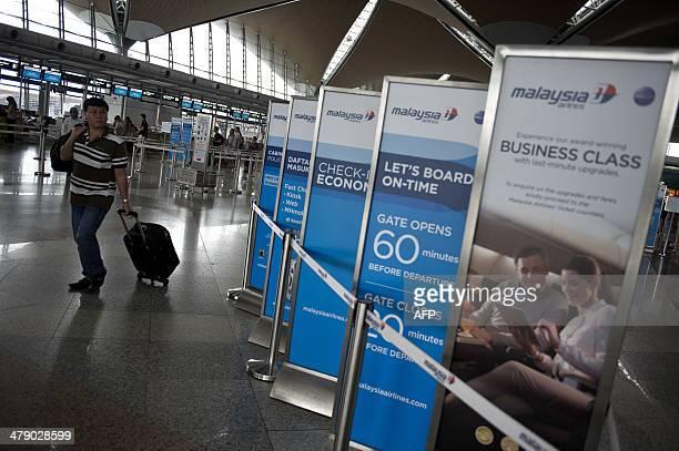 A passenger walks past Malaysia Airlines information board at Kuala Lumpur International Airport in Sepang outside Kuala Lumpur on March 16 2014...
