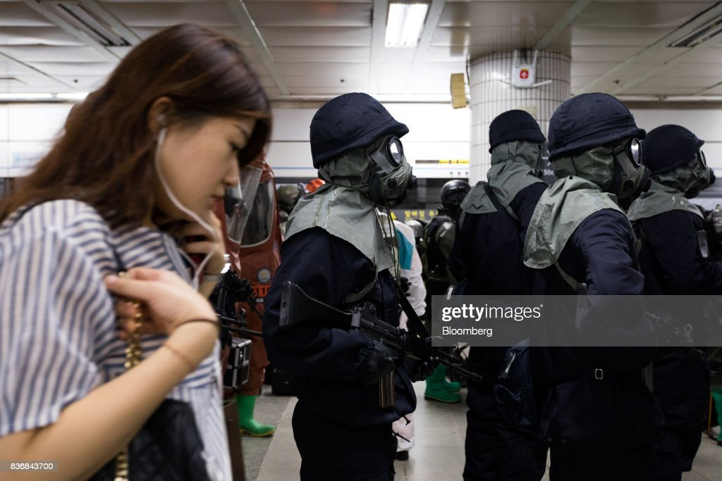 A passenger walks past police officers wearing gas masks during an anti-terror drill on the sidelines of the Ulchi Freedom Guardian (UFG) military exercises at a subway station in Seoul, South Korea, on Tuesday, Aug. 22, 2017. North Korea warned the U.S. on Tuesday it will face 'merciless revenge' for ignoring Pyongyangs warnings over annual military drills with South Korea. Photographer: SeongJoon Cho/Bloomberg via Getty Images
