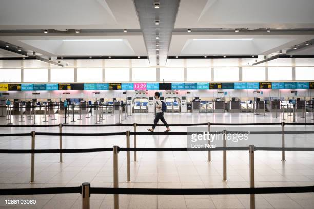 Passenger walks past the deserted check-in desks and passenger facilities in the North Terminal at Gatwick Airport on November 27, 2020 in London,...