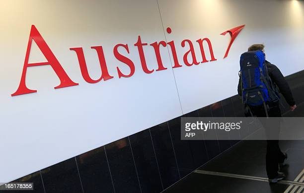 A passenger walks past the logo of Austrian airlines at the Vienna Schwechat international airport in Schwechat some 20km south east of Vienna on...