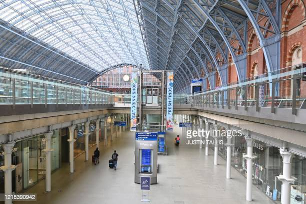 Passenger walks through an almost empty St Pancras train station in central London, on June 8 as the UK government's planned 14-day quarantine for...