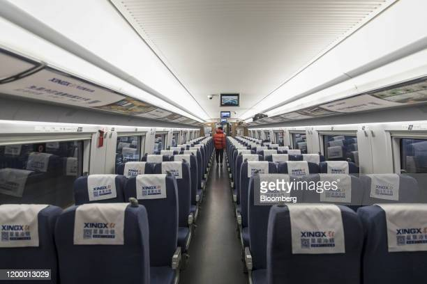 Passenger walks through an empty carriage on a high-speed train destined for Guangzhou as it leaves the station in Shanghai, China, on Tuesday, Feb....