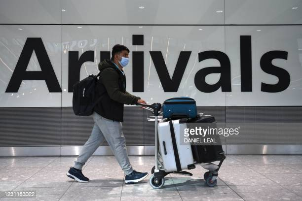 Passenger walks through the arrivals hall at Terminal 5, Heathrow Airport in west London on February 15, 2021. - The government from today will...