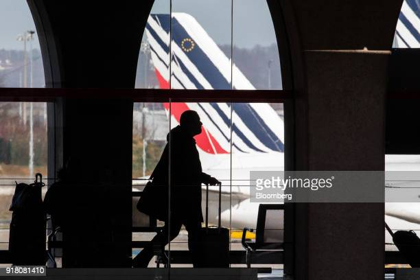 A passenger walks through the terminal as Tricolour livery sits on the tail fin of an Air France passenger aircraft beyond operated by Air FranceKLM...