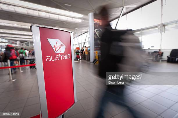 A passenger walks to check in at the Virgin Australia Holdings Ltd area at the domestic terminal of Sydney airport in Sydney Australia on Wednesday...