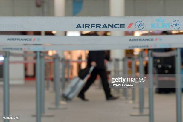A passenger walks toward the checkin desk as Air France employees protest against a restructuring plan that will cut hundreds of jobs next year on...
