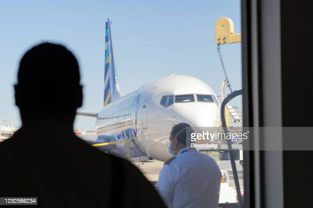 Passenger watches a pilot in front of a Boeing Co. 737-800 aircraft operated by Avelo Airlines ahead of the airline's inaugural flight at Hollywood...