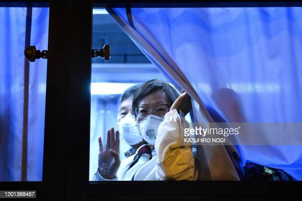 A US passenger waves to reporters while arriving at the Haneda Airport in Tokyo on February 17 2020 after disembarking in Yokohama from the Diamond...