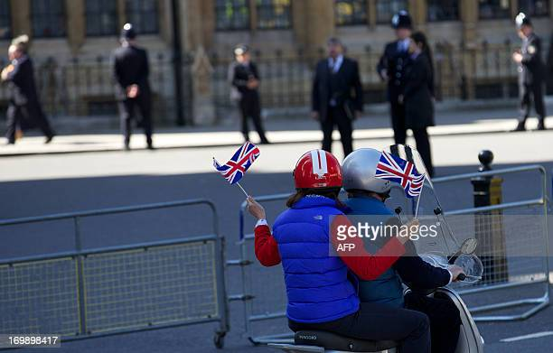 A passenger waves union jack flags from the back of a scooter outside Westminster Abbey in London on June 4 2013 before the Queen attends a ceremony...
