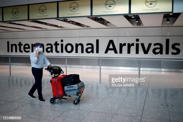 A passenger wearing a face mask and a visor as a precaution against the novel coronavirus arrive at Heathrow airport west London on May 22 2020...