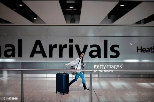 Passenger wearing a face mask as a precaution against the novel coronavirus arrive at Heathrow airport, west London, on May 22, 2020. - Travellers...