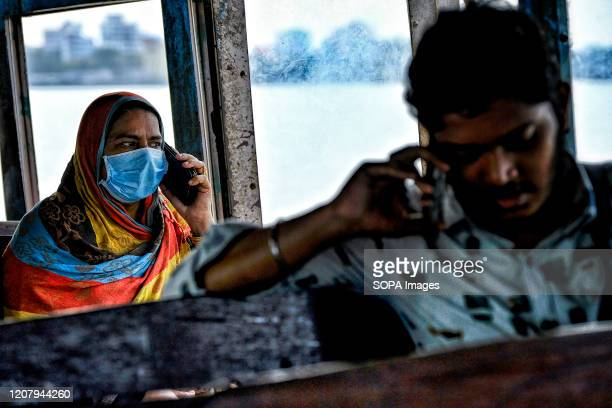 Passenger wearing a face mask as a precaution against the spread of Coronavirus sits in a ferry. With 298 confirmed coronavirus cases, India has...
