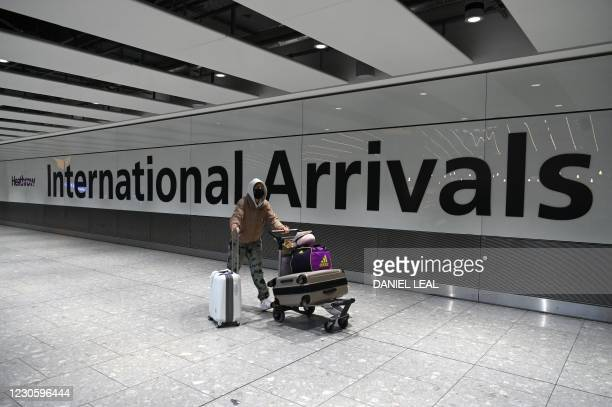 Passenger wearing a face mask as a precautionary measure against COVID-19, walks through the arrivals hall after landing at London Heathrow Airport...