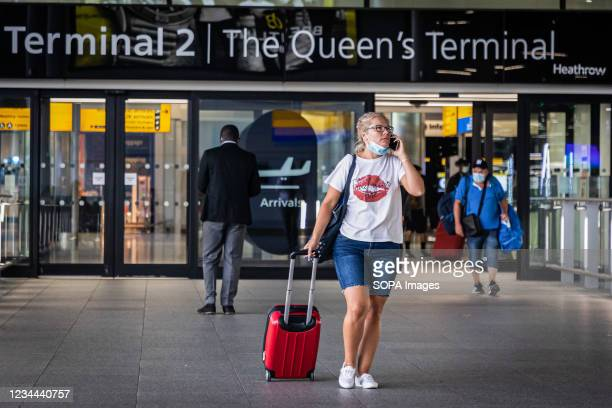 Passenger wearing a face mask as a preventive measure against the spread of coronavirus arrive at Heathrow Airport Terminal 2 in London. From...