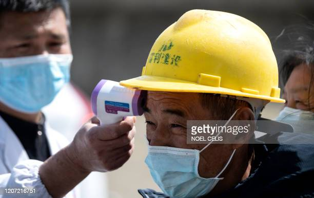 A passenger wearing a face mask has his temperature checked before commuting on a boat in Jiujiang across the Yangtze river the border between Chinas...