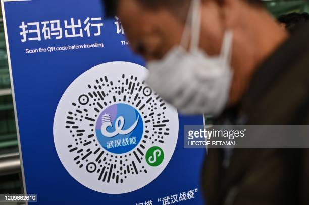 Passenger wearing a face mask walks past a Wuhan city health QR code, to be scanned before entering Tianhe Airport in Wuhan, China's central Hubei...