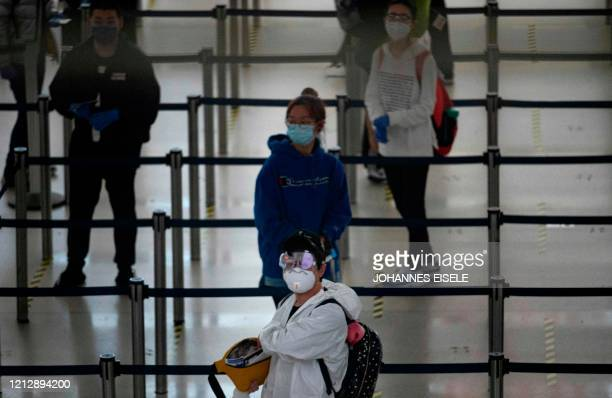 Passenger wearing a facemask and protective suit waits for a flight at Terminal 1 of John F. Kennedy Airport amid the novel coronavirus pandemic on...