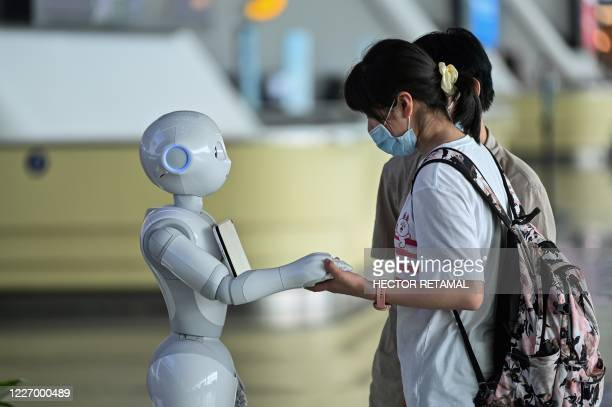 Passenger wearing a facemask as a preventive measure against the COVID-19 coronavirus uses an information robot at Tianhe Airport in Wuhan, in Chinas...