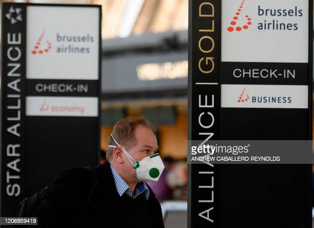 A passenger wearing a mask as a precaution against COVID19 walks past a Brussels Airlines checkin area at Dulles International airport in Dulles...