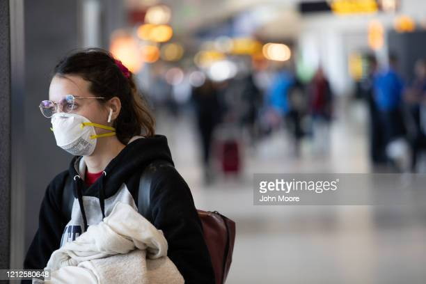 A passenger wearing a mask prepares to board a flight departing the SeattleTacoma International Airport on March 15 2020 in Seattle Washington The...