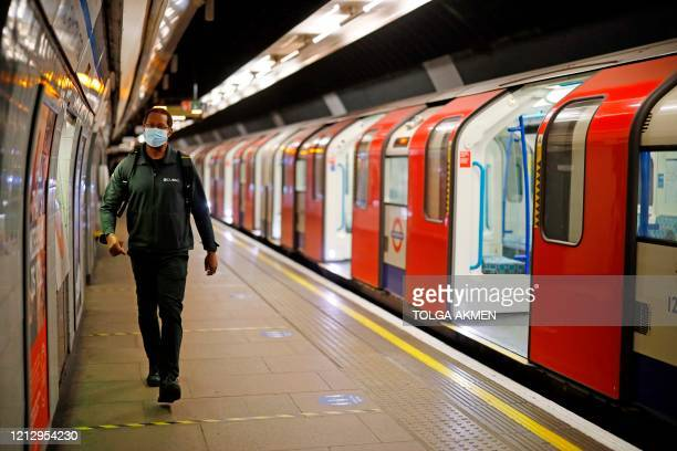 Passenger wearing a mask walks along the platform at Vauxhall Underground station in London on May 14, 2020 after a partial loosening of the...
