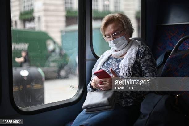 Passenger wearing a protective face covering to combat the spread of the coronavirus, checks her phone while travelling on a bus along Oxford Street...