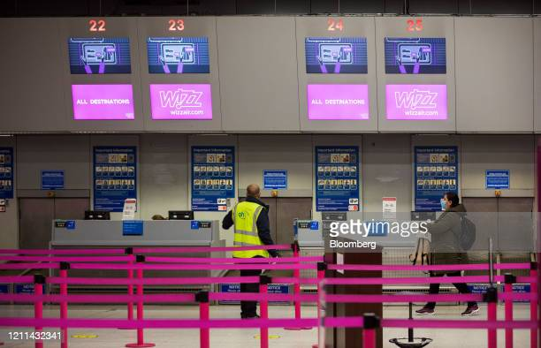 A passenger wearing a protective face mask approaches the checkin area for Wizz Air Holdings Plc at London Luton Airport in Luton UK on Friday May 1...