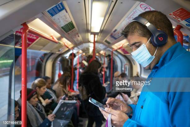 A passenger wearing a protective face mask checks his mobile phone while travelling on the Central Line of the London Underground in London UK on...