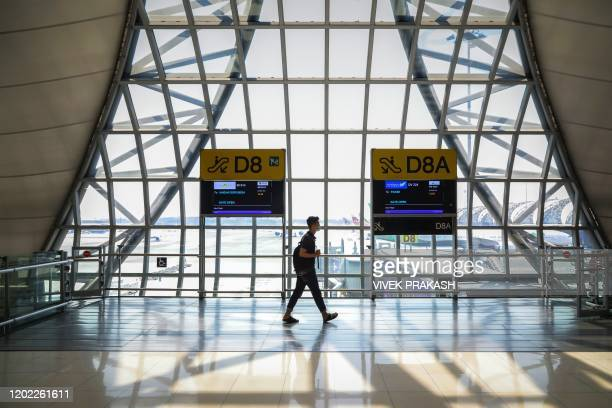 Passenger wearing a protective face mask walks through a normally busy area at Suvarnabhumi Airport in Bangkok on February 21, 2020.