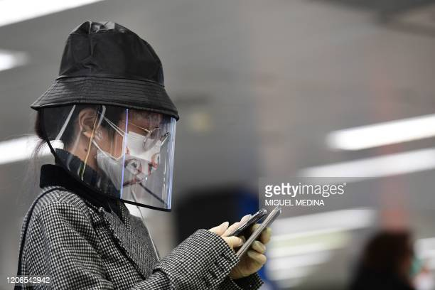 Passenger wearing a protective mask and a plastic face shield checks her smartphone as she waits to check in at Milan's Linate airport on March 11 a...