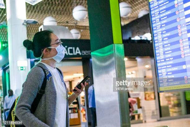 """March 11: A passenger wearing a protective mask checks a electronic board in the airport on March 11, 2020 in Lisbon, Portugal. """"nThe International..."""