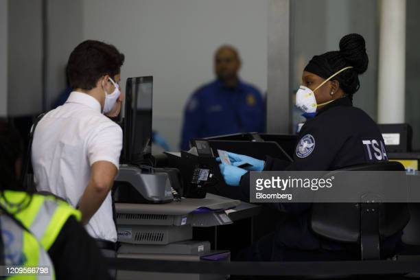 Passenger wearing a protective mask enters a Transportation Security Administration checkpoint at Los Angeles International Airport in Los Angeles,...