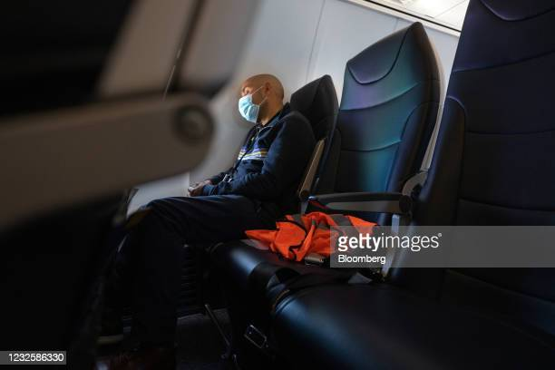 Passenger wearing a protective mask sleeps during the Avelo Airlines inaugural flight from Hollywood Burbank Airport in Burbank, California, to...