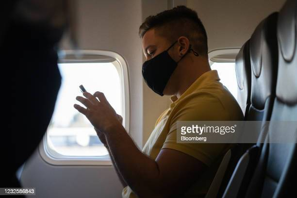 Passenger wearing a protective mask uses a mobile phone before an Avelo Airlines flight at Charles M. SchulzSonoma County Airport in Santa Rosa,...