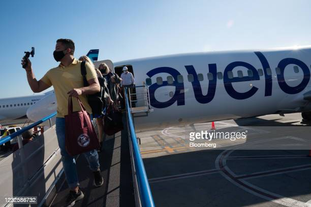 Passenger wearing a protective mask uses a recording device while disembarking from a Boeing Co. 737-800 jetliner operated by Avelo Airlines at...