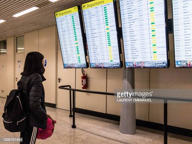 A passenger wearing a protective respiratory mask to prevent the spread of the new coronavirus checks a departure timetable board at Rome's Fiumicino...