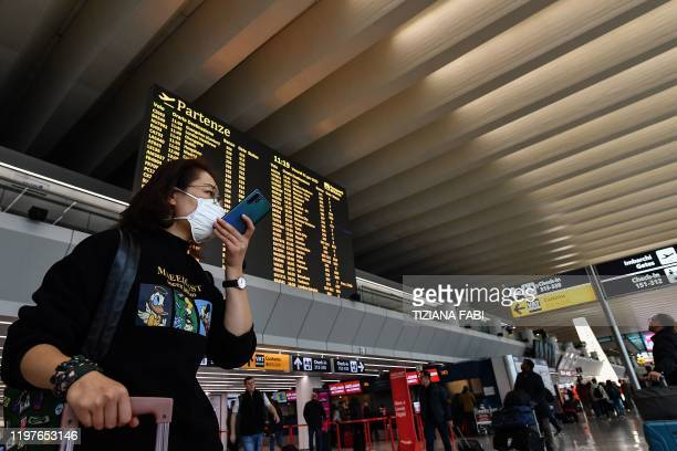 A passenger wearing a respiratory mask speaks on her smartphone by the departures board on January 31 2020 at Rome's Fiumicino airport as a number of...