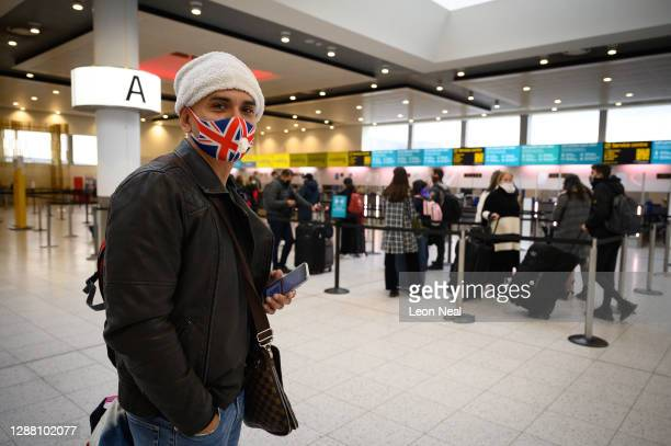Passenger wearing a Union Flag face mask waits in the North Terminal to board one of the few flights departing at Gatwick Airport on November 27,...