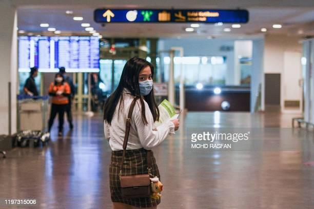 A passenger wearing face mask holds a health advisory card upon arrival at the Kuala Lumpur International Airport 2 in Sepang on January 29 2020...