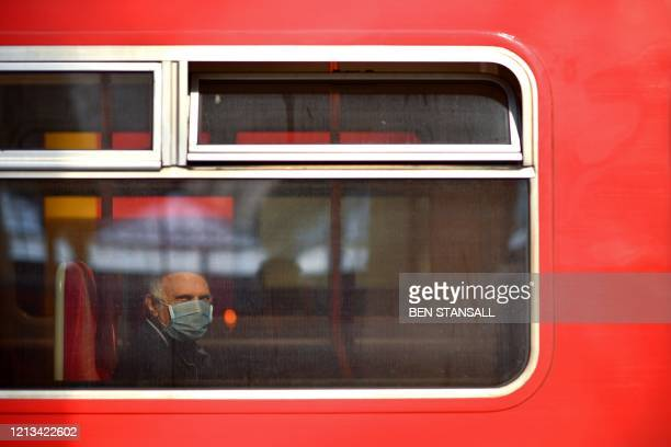A passenger wearing PPE including a face mask as a precautionary measure against COVID19 sits aboard a train as it arrives at Waterloo Train station...
