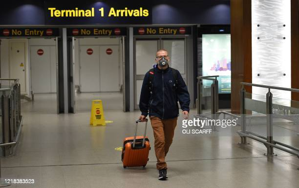 Passenger wearing PPE , including a face mask as a precautionary measure against COVID-19, arrives at Terminal 1 of Manchester Airport in northern...