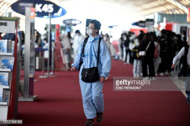 Passenger wearing protective clothing walks prior to boarding a China Southern Airlines for Canton Guangzhou Roissy-Charles de Gaulle Airport on the...